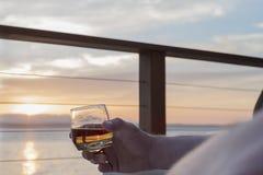 Uísque à disposição no por do sol na plataforma pelo mar Imagens de Stock Royalty Free