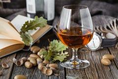 Uísque ambarino da cor do oа de vidro no vidro na tabela de carvalho Foto de Stock
