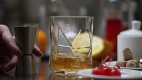 U?sque de derramamento do empregado de bar no vidro com os cubos de gelo na tabela de madeira e no fundo escuro preto, foco em cu video estoque