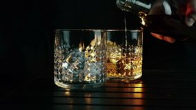 Uísque de derramamento do empregado de bar nos dois vidros com os cubos de gelo na tabela de madeira e no fundo escuro preto, foc vídeos de arquivo