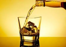 Uísque de derramamento do empregado de bar no vidro na tabela com reflexão, atmosfera morna do matiz Foto de Stock Royalty Free
