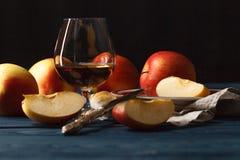 Uísque e maçãs na tabela de madeira escura Imagem de Stock Royalty Free