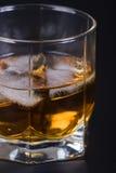 Uísque em um vidro com gelo Imagens de Stock