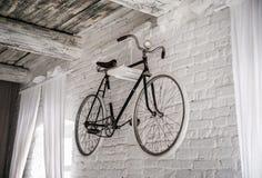 Uíste branco velho da bicicleta em uma parede de pedra branca fotos de stock