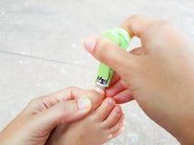 Uñas asiáticas del pie del ` s del bebé del corte de la madre del primer con el clavo Foto de archivo libre de regalías