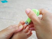 Uñas asiáticas del pie del ` s del bebé del corte de la madre del primer con el clavo Fotos de archivo