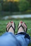 Uñas del dedo del pie rojos, pies de la mujer Foto de archivo libre de regalías