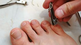 Uñas del pie del corte del hombre con las podadoras Uñas del pie del corte del varón a pie Primer del pie y de los dedos del pie  almacen de metraje de vídeo
