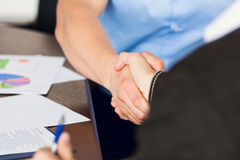 Uścisk dłoni dwa biznesmena na tle sekretarka Obraz Royalty Free