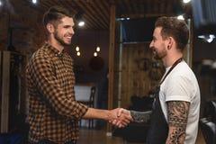 Uścisk dłoni dwa faceta przy zakładem fryzjerskim obrazy stock