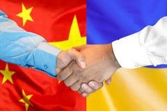 Uścisk dłoni na Chiny i Ukraina fladze tło zdjęcia stock