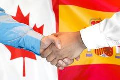 Uścisk dłoni na Hiszpania i Kanada fladze tło zdjęcie stock