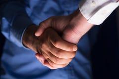 Uścisku dłoni Handshaking w zmroku z niskim światłem obraz stock