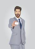 Uśmiechać się dobrze ubierającego biznesmena pokazuje wizytówkę Zdjęcie Royalty Free