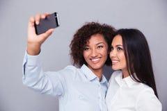 Uśmiechać się dwa dziewczyny robi selfie fotografii na smartphone Obraz Stock