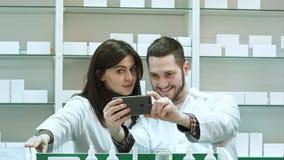 Uśmiechać się dwa farmaceuty bierze selfie w aptece Zdjęcie Stock