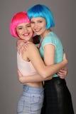 Uśmiechać się modelów w kolorowych perukach trzyma ręki i pozować z bliska Szary tło Zdjęcie Royalty Free