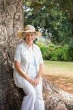 Uśmiechać się przechodzić na emeryturę kobiety obsiadanie na drzewnym bagażniku fotografia stock