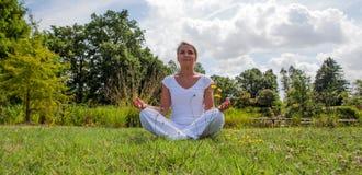 Uśmiechać się 20s blond dziewczyny medytuje w zielonych surrondings Zdjęcia Royalty Free