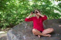 Uśmiechać się 20s dziewczyny obserwuje jej środowisko z lornetkami Zdjęcia Royalty Free