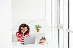 Uśmiechać się skoncentrowanej afrykańskiej kobiety używa laptop fotografia royalty free