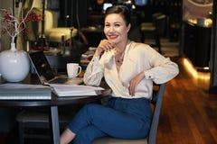 Uśmiechać się zrelaksowanego Azjatyckiego bizneswomanu obsiadanie w kawiarni zdjęcia stock