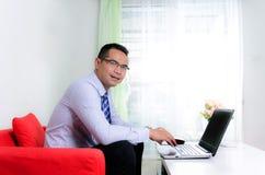 Uśmiecha się azjatykciego biznesowego mężczyzna używa laptop w jego do domu Obraz Stock