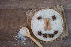 Uśmiecha się zdrowych, Surowych ryż, Ryżowy grian, w pucharze drewnianym z cynamonem i gwiazdowym anyżem, odgórny widok zdjęcie stock
