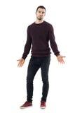 Uśmiechający się intryguję mężczyzna być ubranym wałkoni się pulower z rozciągniętych ręk przyglądający up zdjęcie royalty free