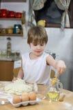 Uśmiechający się Little Boy Ma zabawę Robi ciastu na Kuchennym stole Fotografia Stock
