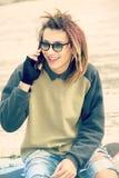 Uśmiechający się opowiadać z mądrze telefonu outdoors ciepłymi brzmieniami filtruje appl Zdjęcie Stock