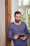 Uśmiechający się relaksującego mężczyzna trzyma pastylkę komputerowa Obrazy Stock