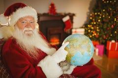Uśmiechający się Santa wskazuje jego palcowego na kuli ziemskiej Obrazy Royalty Free