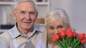 Uśmiechający się starzejącego się pary obejmowanie, kobieta wącha kwiaty, świętuje rocznicę zbiory