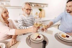 Uśmiechający się starzejącej się pary cieszy się gościa restauracji z synem w domu Obrazy Stock