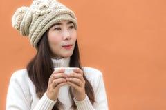 Uśmiechający się twój azjatykcią kobiety rękę trzyma białą filiżankę kawy przy zimy pogodą, colour pełnego tło Zdjęcie Royalty Free