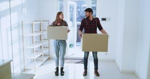 Uśmiechający się z podnieceniem i czujący nowa para małżeńska rusza się nowy przestronny dom poruszający dnia nieść zdjęcie wideo