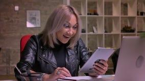 Uśmiechający się zdziwionego pojawienie blondynka caucasian bizneswoman który używa jej pastylkę energetically i szczęśliwie podc