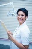 Uśmiechnięci żeńscy dentysty czytania raporty Obrazy Stock