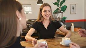 Uśmiechnięci barista dziewczyny serw młoda para filiżanka kawy w sklepie z kawą zbiory