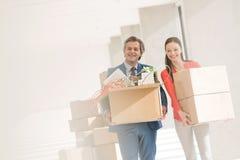 Uśmiechnięci biznesmena i bizneswomanu przewożenia kartony w nowym biurze Fotografia Royalty Free