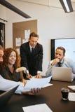 Uśmiechnięci biznesmeni dyskutuje papierkową robotę w biurowym boardro zdjęcia royalty free