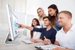 Uśmiechnięci biznesmeni używa komputer stacjonarnego Zdjęcia Royalty Free