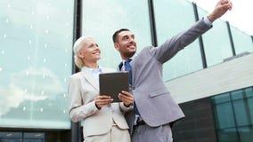 Uśmiechnięci biznesmeni z pastylka komputerem osobistym outdoors Obrazy Stock