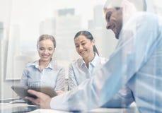 Uśmiechnięci biznesmeni z pastylka komputerem osobistym w biurze Fotografia Royalty Free