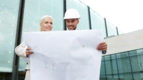 Uśmiechnięci biznesmeni z projektem i hełmami Zdjęcie Stock