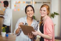 Uśmiechnięci bizneswomany w biurze Zdjęcie Royalty Free