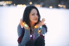 Uśmiechnięci brunetki kobiety mienia sznurka światła Obraz Royalty Free
