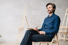 Uśmiechnięci Dojrzali artysty rysunku nakreślenia w studiu obraz stock
