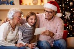 Uśmiechnięci dziadkowie z wnuczki dopatrywania częścią i fotografią Zdjęcia Royalty Free